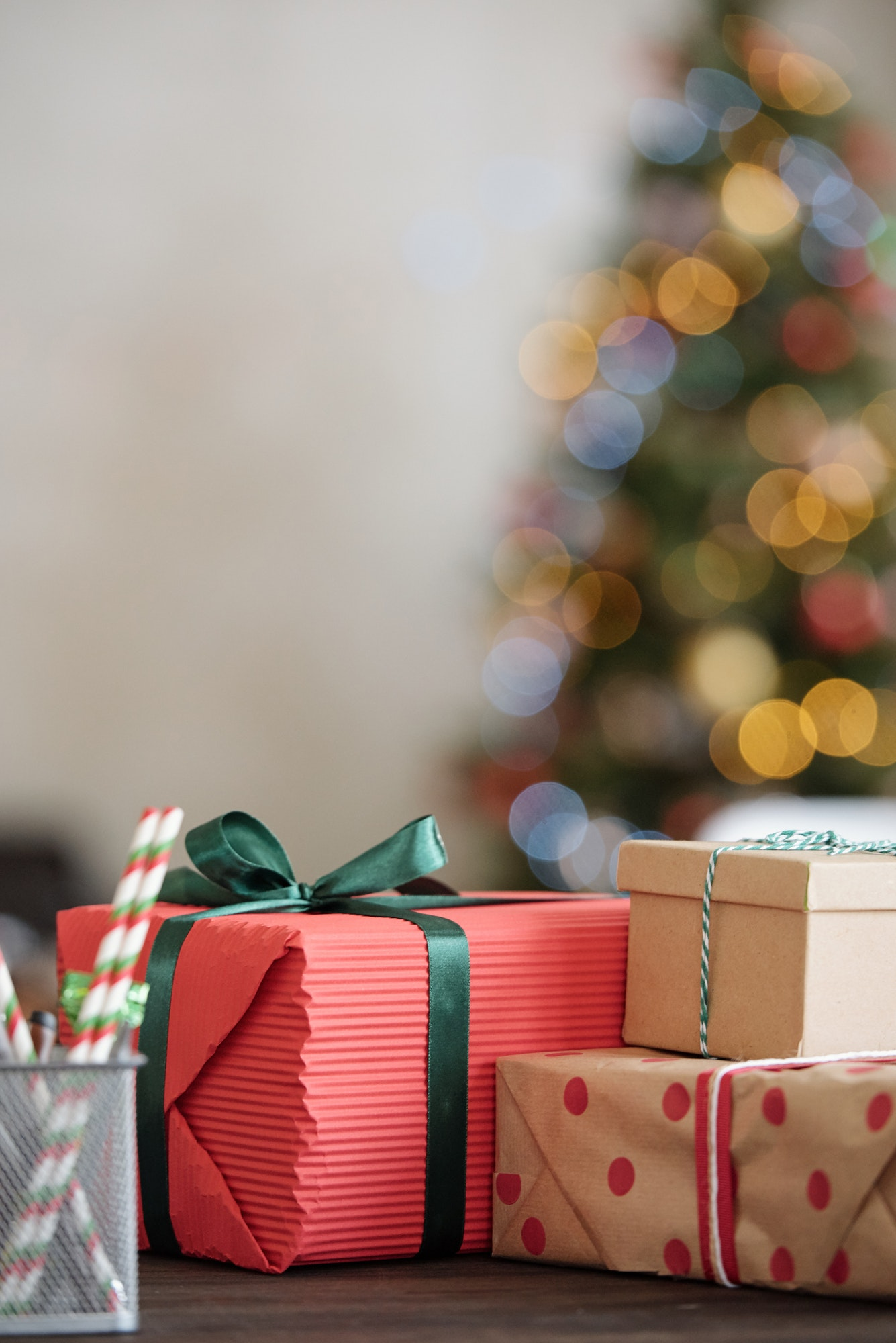 Group of packed Christmas gifts on table in front of camera against xmas tree
